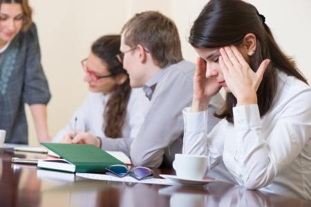 Jong moe zakelijke vrouw met hoofdpijn zitten op seminar