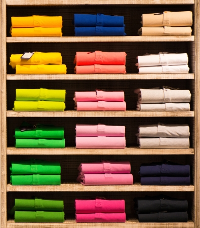 clothing: Various colour shirts at shelf in shop