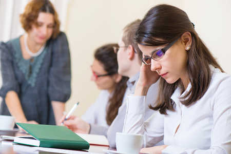 worried woman: Young tired business woman with headache sitting at seminar