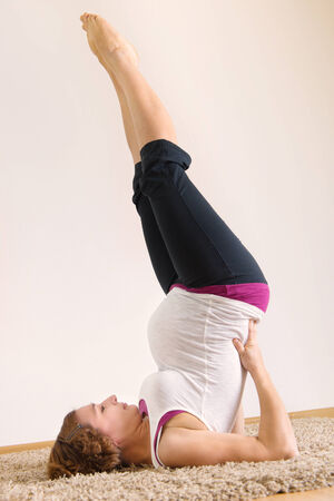 Young pregnant woman doing yoga execises at home photo