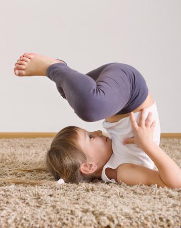 children background: Poco de yoga linda chica ejercicio en casa Foto de archivo