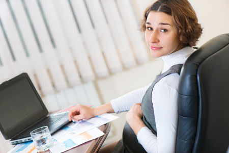 Young pregnant woman in dress working at office photo