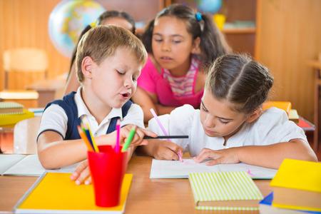 niños latinos: Los estudiantes de primaria felices en el aula en la escuela Foto de archivo