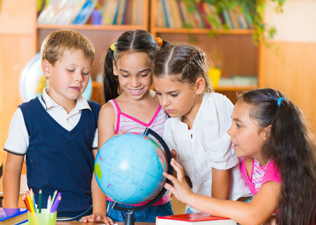 human geography: Happy elementary students in classroom at school