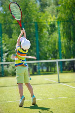 Little cute boy playing tennis on green court photo