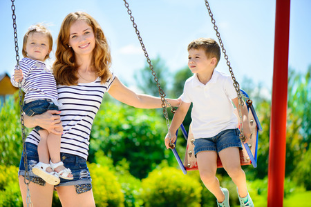 Šťastná matka a její děti na dětském hřišti Reklamní fotografie