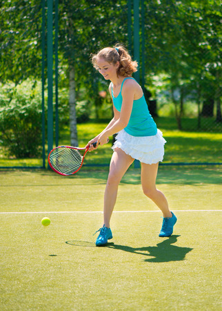 Portrait of young beautiful woman playing tennis in summer  photo