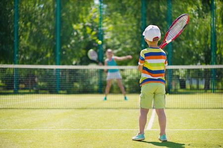 녹색 코트에서 작은 귀여운 소년의 연주 테니스