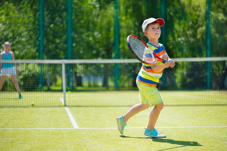 jugando tenis: Poco lindo ni�o jugando tenis en la pista verde Foto de archivo