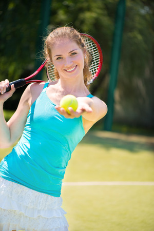 Portrait of  pretty young tennis player on the court  photo