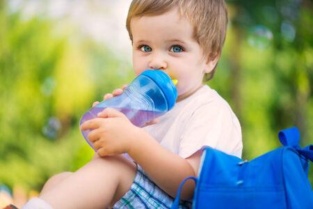 Cute little boy drinking water from bottle photo