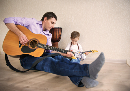 teaching music: Young father with his little son playing guitar Stock Photo