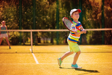 Little cute boy playing tennis on green court photo