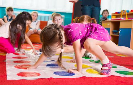 Leuke peuters spelen in twister spel op de kleuterschool