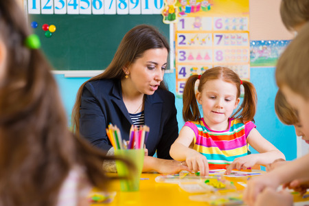 niños estudiando: Niños lindos que lección apliques en el jardín de infantes Foto de archivo