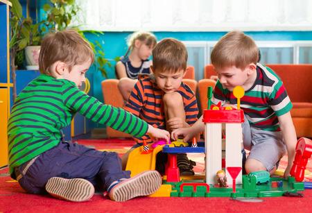 Cute little boys playing on the floor at kindergarten