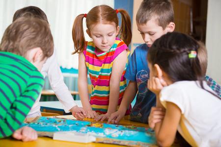 niños jugando en la escuela: Niños en edad preescolar lindo plaing juego de geografía en la mesa Foto de archivo