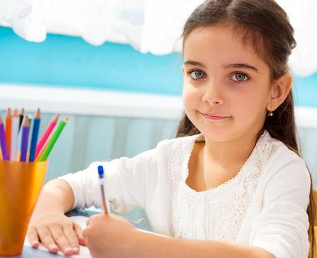 schoolchild: Schattige kleine Spaanse meisje schrijven op school