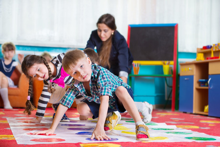 nursery room: Cute toddlers playing in twister game at kindergarten