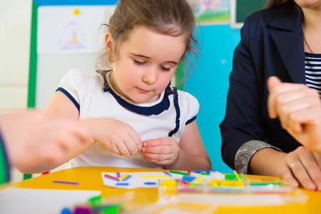 Cute little children having applique lesson at kindergarten photo