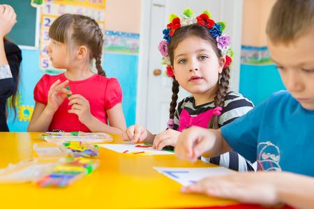 educators: Niños lindos en la lección en el jardín de infantes