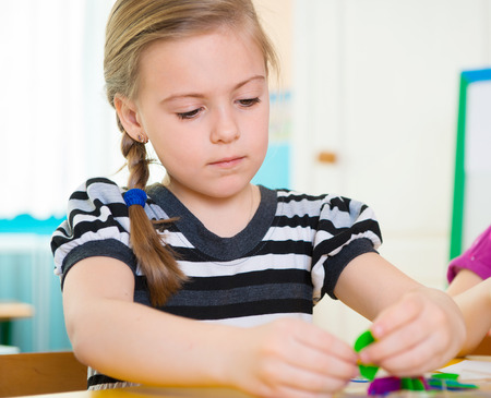 Cute little girl on lesson at kindergarten photo