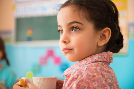 Cute little hispanic girl with cup of milk at daycare Standard-Bild