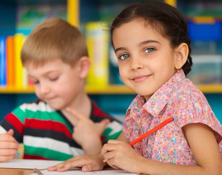 Filhinhos bonitos que desenham e que estudam na creche