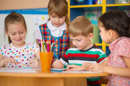 Cute little children drawing and studying at daycare