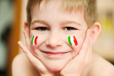 italien flagge: Netter kleiner Junge mit europäischen Flaggen auf den Wangen Lizenzfreie Bilder