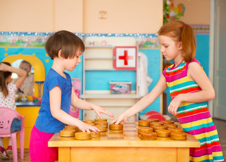 Two cute little girls playing in checkers at kindergarten photo
