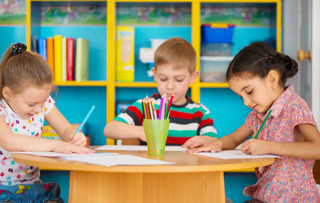 daycare: Three cute preschool children drawing at daycare Stock Photo