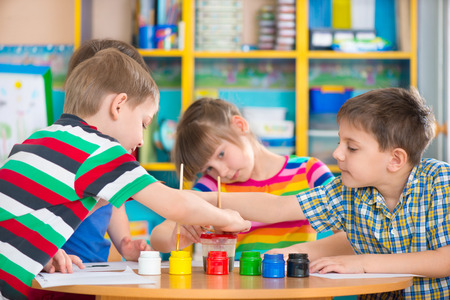 Cute little preschool children drawing with colorful paints at kindergarten photo