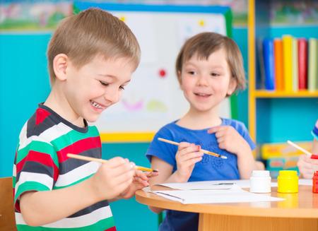 Lindos niños preescolares dibujando con pinturas de colores en el jardín de infantes