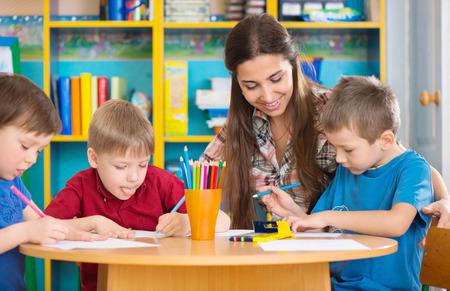 Cute little children drawing with teacher at preschool class photo
