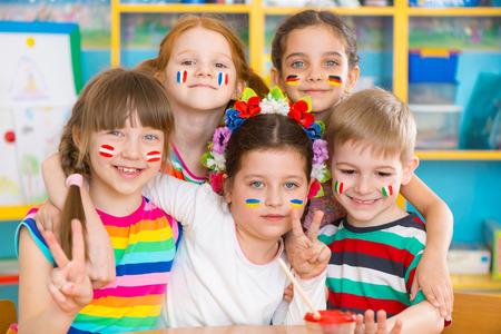 campamento: Niños felices en el campamento de lenguaje con banderas en las mejillas