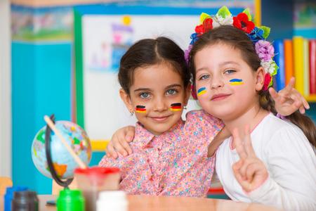 niños latinos: Dos niñas felices en el campamento internacional de verano con banderas en las mejillas