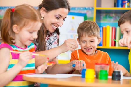 maestra preescolar: Niños lindos dibujo con el maestro en la clase de preescolar