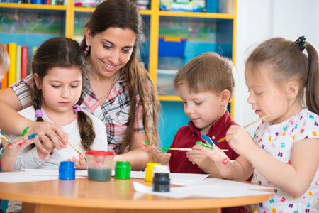preschool children: Cute little children drawing with teacher at preschool class Stock Photo