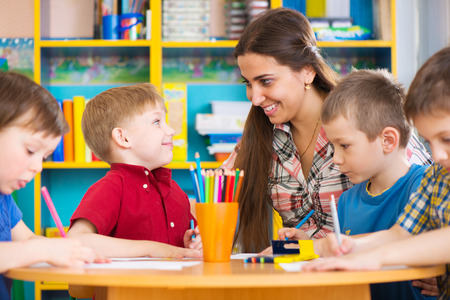 Cute little children drawing with teacher at preschool class Stock Photo