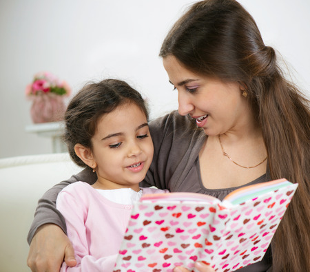Cute little girl reading book with mother at home photo