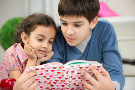 Brother and cute little sister reading book at home photo