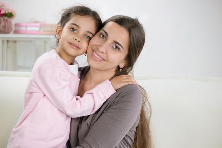 niños latinos: Madre joven feliz con su hija en su casa Foto de archivo