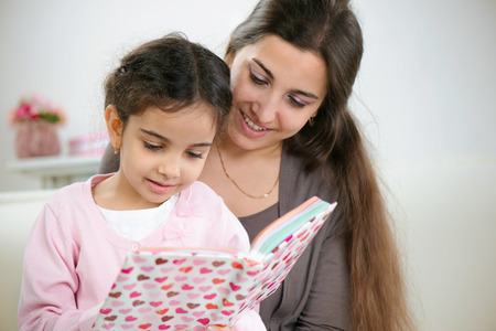Cute little girl reading book with mother at home Stock Photo