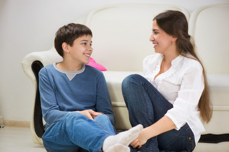 Cute teen boy with his young mother at home Stock Photo