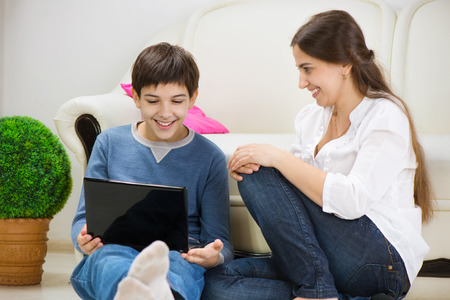Teen son with young mother with laptop at home