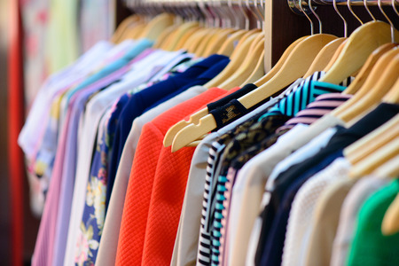 Variety of clothes hanging on rack in boutique Stock Photo