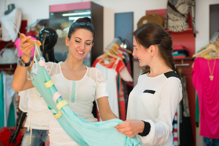 Two young women in clothes boutique choosing dress photo