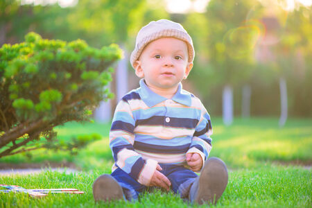 Little baby boy playing on green grass photo