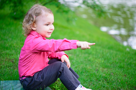 Sweet little girl outdoors with curly hair in park Stock Photo - 29038777